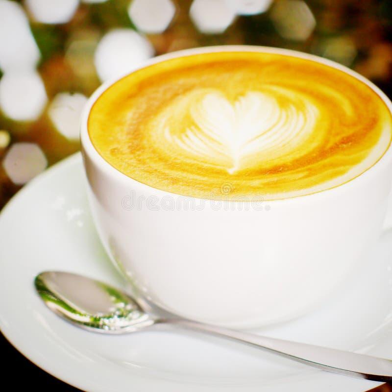 与心脏形状,减速火箭的作用的热奶咖啡或拿铁咖啡 免版税图库摄影