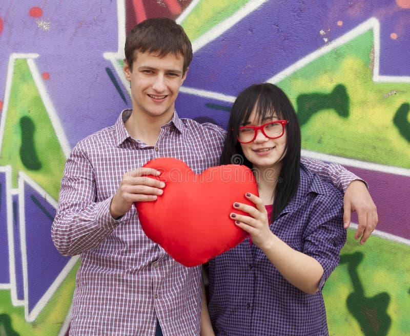 与心脏的十几岁在街道画墙壁附近。 库存图片