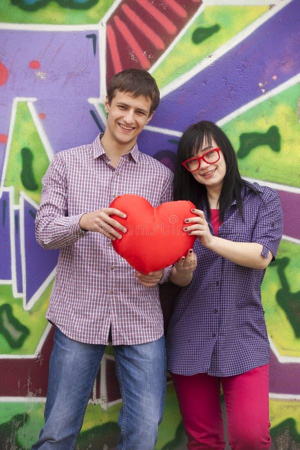 与心脏的十几岁在街道画墙壁附近。 免版税库存照片