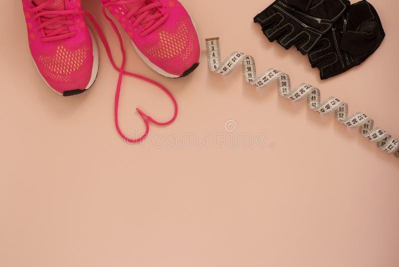 与心脏的时尚时髦教练员 爱,行家集合 女性运动鞋,体育穿上鞋子米,并且在舱内甲板的训练手套放置样式, t 免版税库存照片