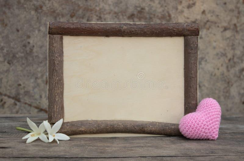 与心脏的木制框架在木桌上 免版税库存图片
