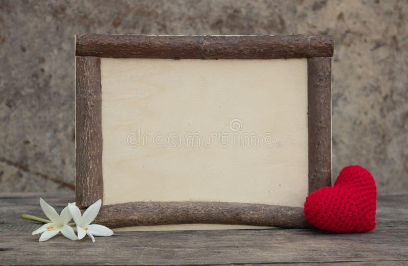 与心脏的木制框架在木桌上 免版税库存照片