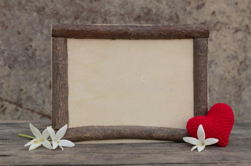 与心脏的木制框架在木桌上 库存图片