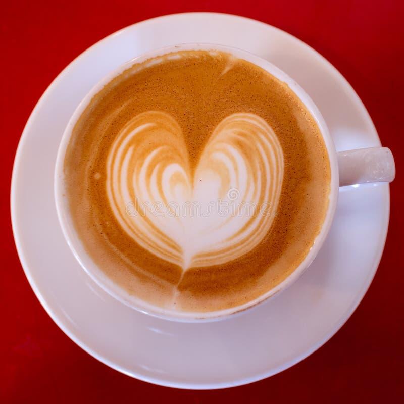 与心脏的热奶咖啡在白色杯子 库存图片