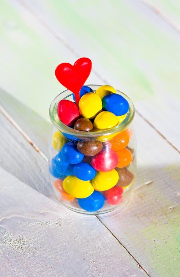 与心脏的色的糖果在玻璃瓶子 免版税库存照片