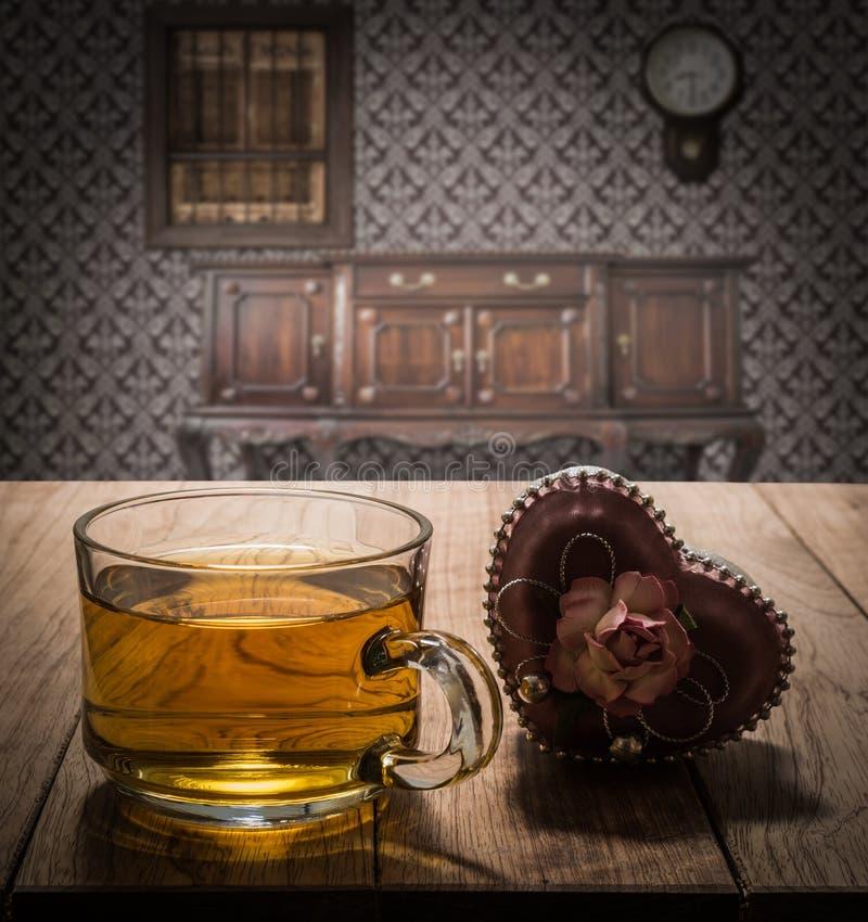 与心脏礼物的茶时间在木桌上 免版税图库摄影