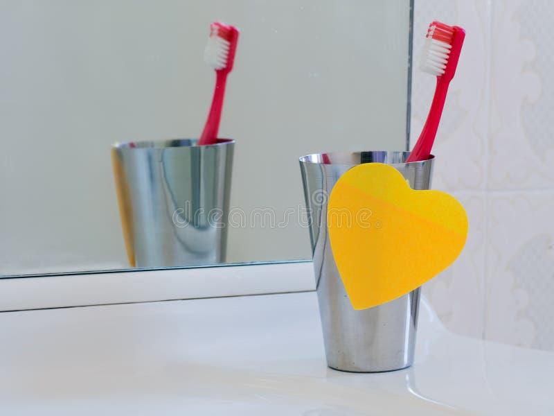 与心脏稠粘的笔记和牙刷的卫生间水槽 爱您的t 免版税图库摄影