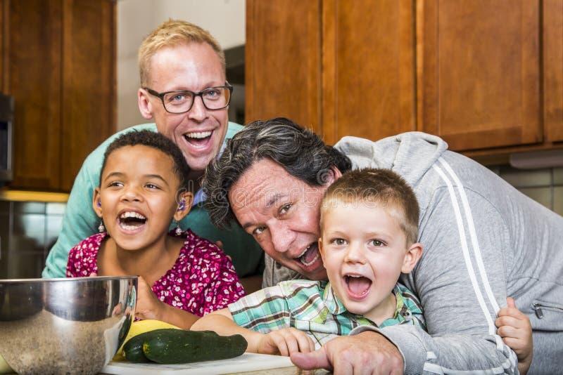 与快乐爸爸的笑的家庭在厨房里 免版税库存照片