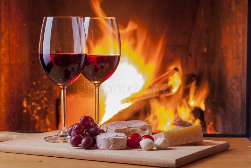 与快餐和葡萄的红葡萄酒在壁炉 库存图片