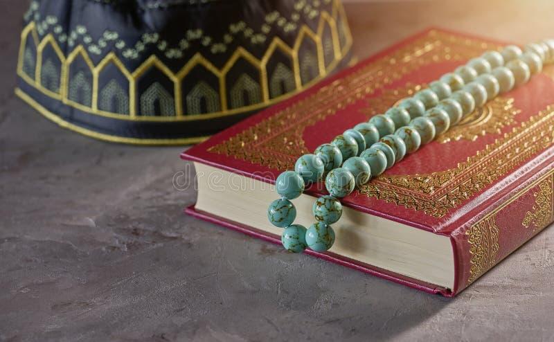 与念珠小珠的圣洁古兰经和穆斯林的kopiah帽子灰色背景的 库存照片