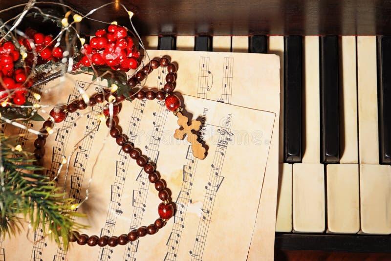 与念珠小珠的圣诞节在钢琴的构成和板料 图库摄影