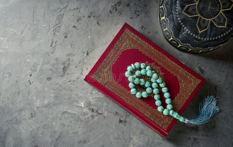 与念珠的伊斯兰教的书古兰经和祈祷在灰色板岩背景的帽子 与拷贝空间的伊斯兰教的概念 库存图片