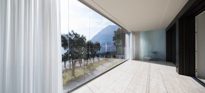 与忽略自然的大窗口的大阳台 免版税库存照片