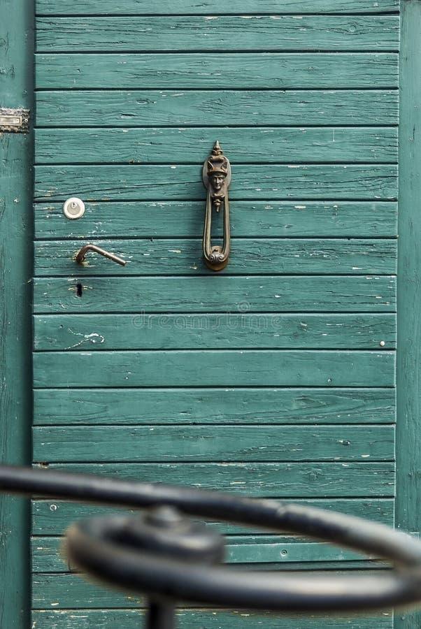 与怀乡通道门环的老,古色古香的木门与在前景的凶恶动机锻铁扶手栏杆 图库摄影