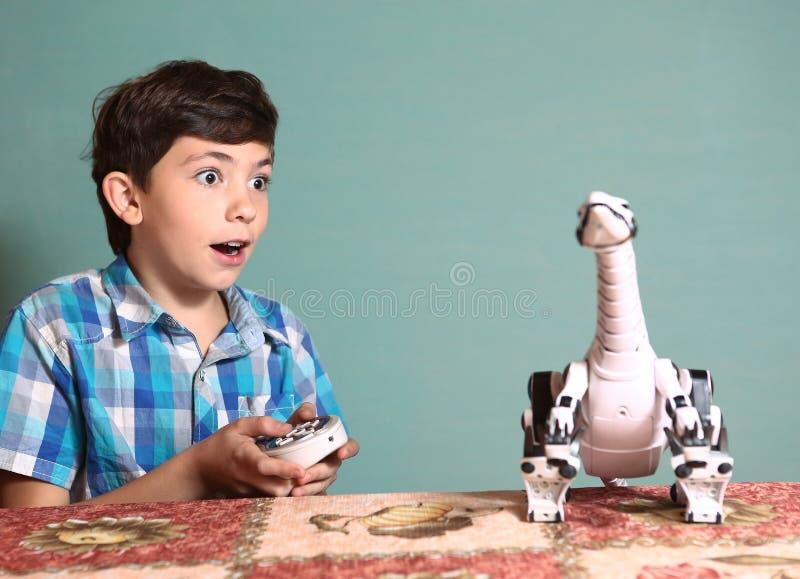 与恐龙玩具的男孩戏剧由遥控pult 免版税库存图片