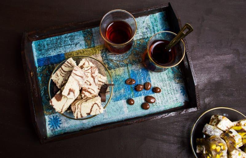 与恶和茶的Halva在板材 免版税图库摄影