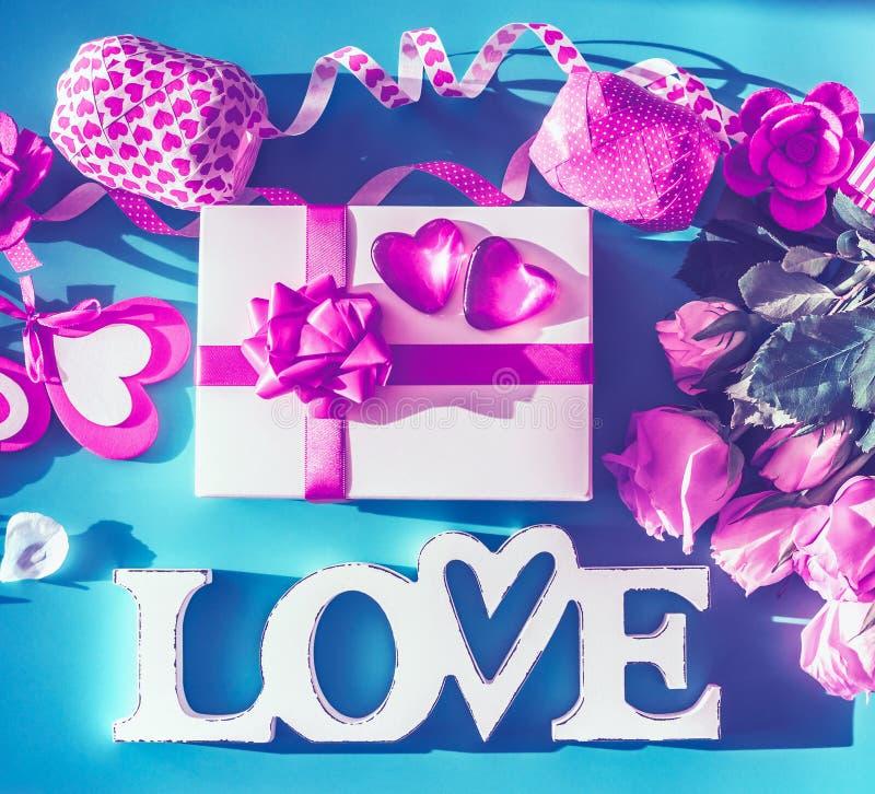 与情书、心脏、浪漫礼物盒、党辅助部件和玫瑰的情人节构成在霓虹颜色,顶视图,fla 免版税图库摄影