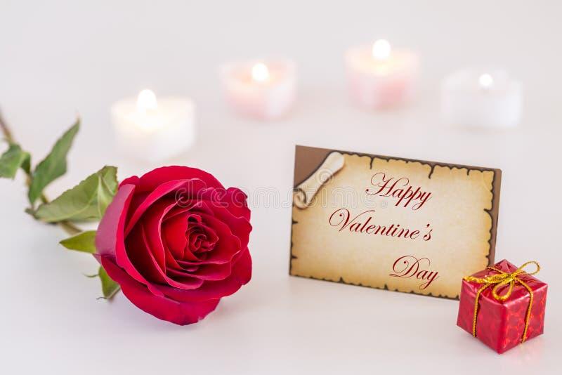 与情人节快乐文本、唯一红色玫瑰、礼物盒和蜡烛光的贺卡在白色' 免版税库存图片