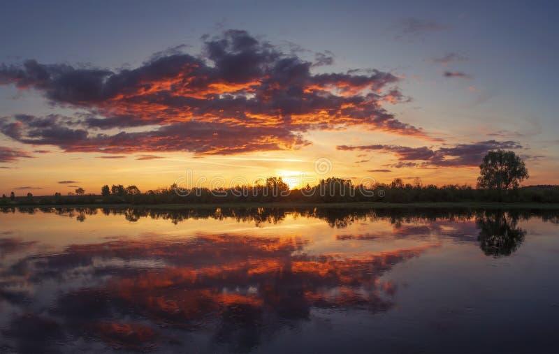 与惊人的天空的美好的五颜六色的夏天日落在河 桃红色,黄色和红色cloudscape 免版税库存图片