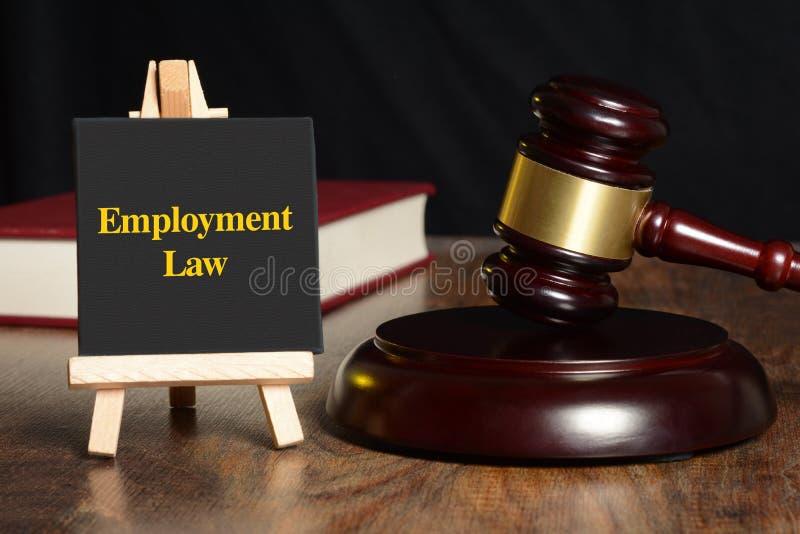 与惊堂木和红色书的雇用法律标志 免版税图库摄影