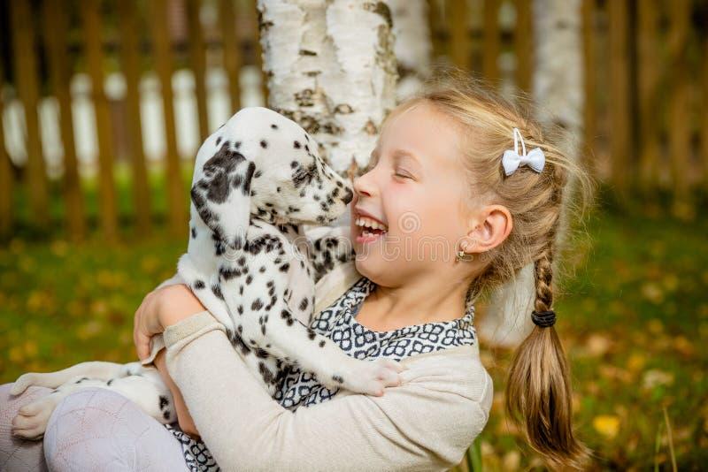 与愉快的所有者的小犬座在获得的公园度过一天演奏和乐趣 笑的女孩滑稽的照片,她拥抱和 免版税库存图片