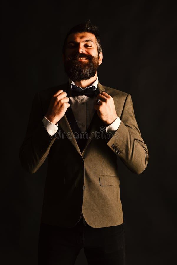 与愉快的面孔的商人调整蝶形领结 企业精神和企业概念 减速火箭的聪明的衣服的人 库存照片