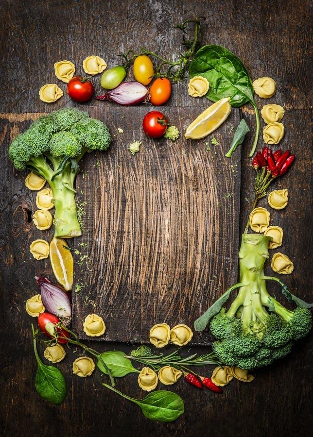 与意大利式饺子面团和新鲜的有机菜的意大利食物概念在黑暗的土气木背景 库存图片