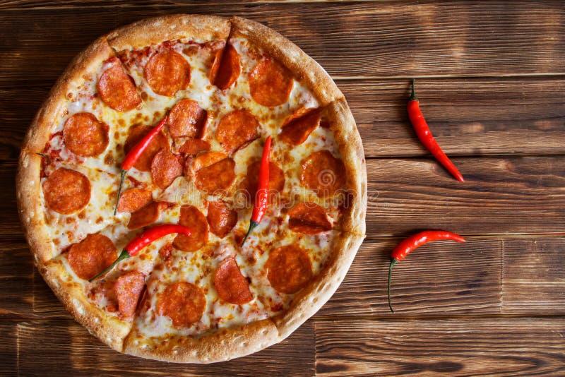 与意大利辣味香肠和红辣椒谎言的切的自创比萨杉木板条自然木表面上  图库摄影