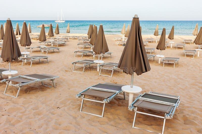 与懒人和闭合的遮阳伞的空的海滩 库存照片