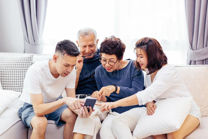 与成人孩子和使用一个手机的资深父母的亚洲家庭和在家放松在沙发一起 库存照片