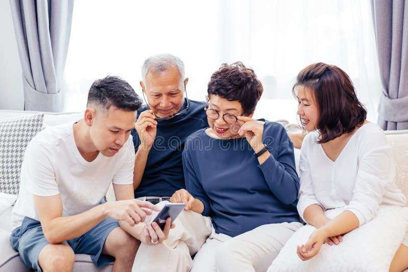 与成人孩子和使用一个手机的资深父母的亚洲家庭和在家放松在沙发一起 库存图片