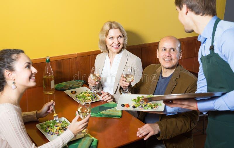 与成人的年轻侍者服务桌在餐馆 免版税库存照片
