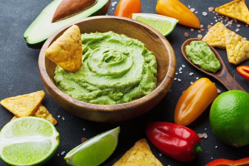 与成份鲕梨、石灰和烤干酪辣味玉米片的鳄梨调味酱捣碎的鳄梨酱调味汁在黑桌上 传统墨西哥食物 库存照片