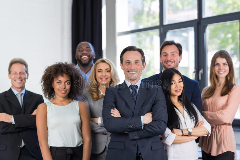 与成熟领导人的上司和商人小组在前景在办公室,领导概念,成功的混合种族队 库存照片