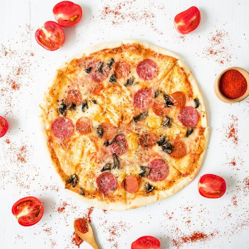 与成份和香料的意大利鲜美薄饼在白色土气背景 平的位置,顶视图 图库摄影