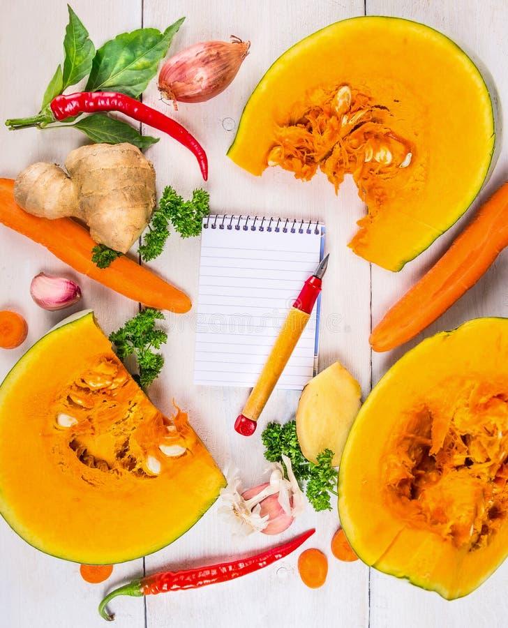 与成份的切口南瓜汤食谱、笔记本和笔的, 免版税库存照片