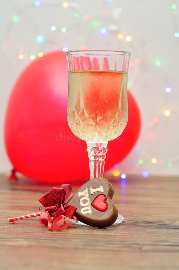 与我爱你词的心脏形状巧克力棒棒糖,一杯香槟和心脏塑造气球 免版税库存照片