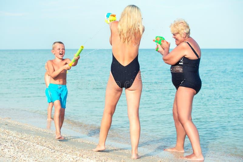 与我的母亲和祖母的儿童游戏有在海滩的水枪的 新的成人 库存图片