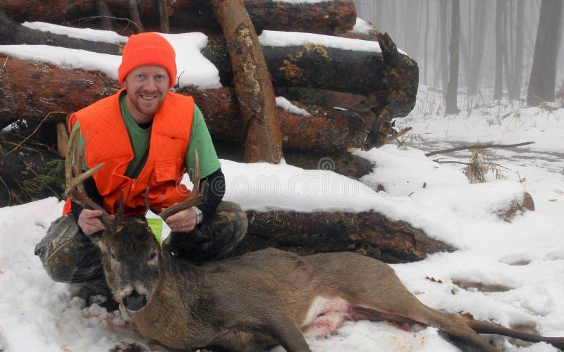 与战利品白尾鹿十点的大型装配架的猎人 免版税库存照片