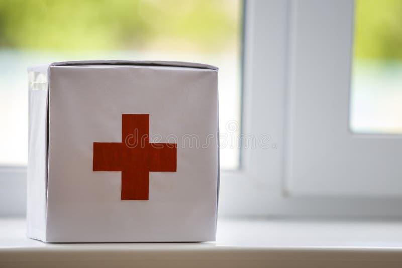 与户内红十字的白色急救工具在被弄脏的背景的窗台 o 免版税库存照片