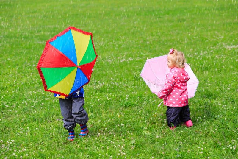 与户外伞的孩子在雨天 库存图片