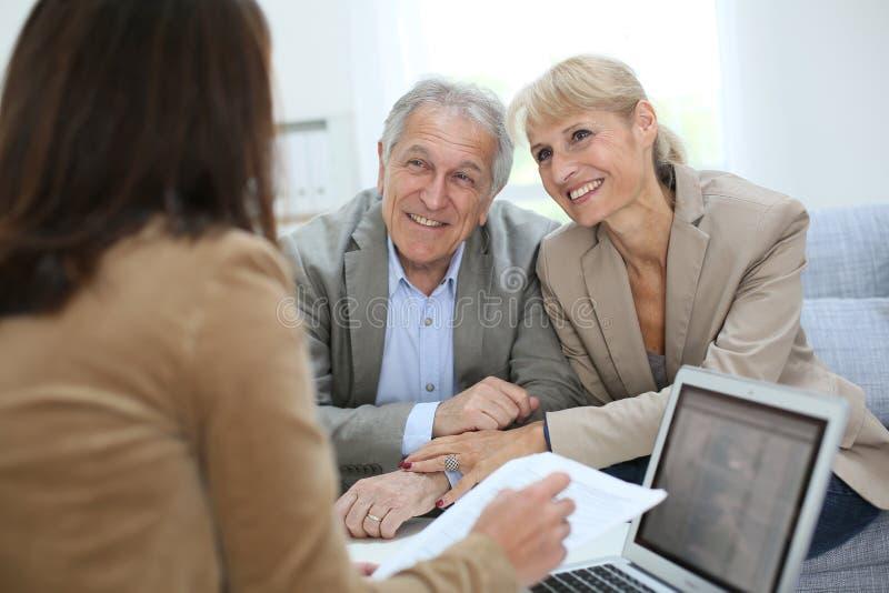 与房地产开发商的资深夫妇会议 库存图片