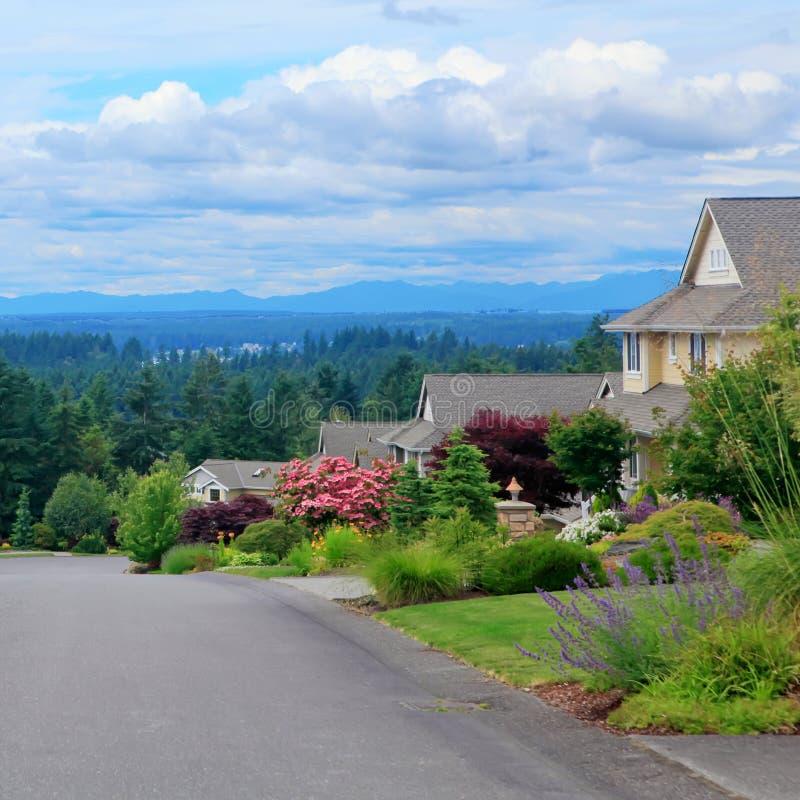 与房子和山景的美丽的stree。 库存图片