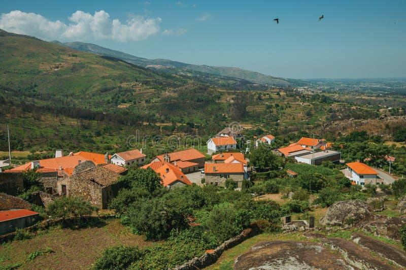 与房子屋顶和岩石的多小山风景 免版税库存图片