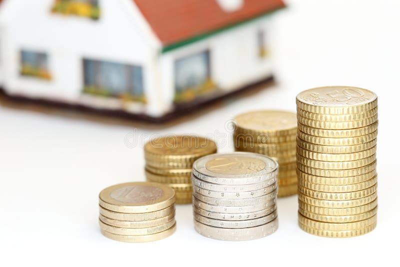 与房子的一些不同的欧洲硬币堆 免版税库存图片