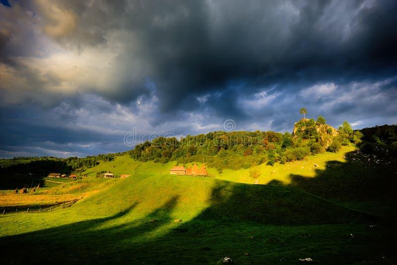 与房子的农村风景夏天某处日出光的在特兰西瓦尼亚 免版税库存照片