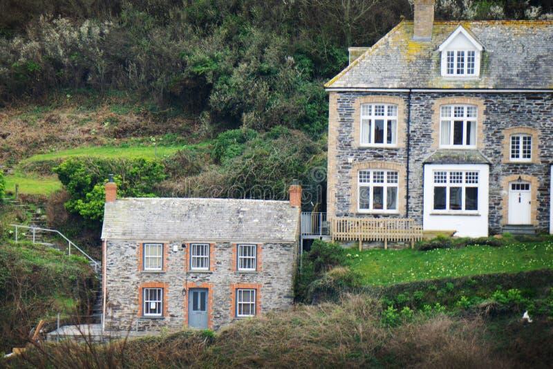 与房子的象草的小山在港以撒,康沃尔郡,英国的上面 免版税库存图片