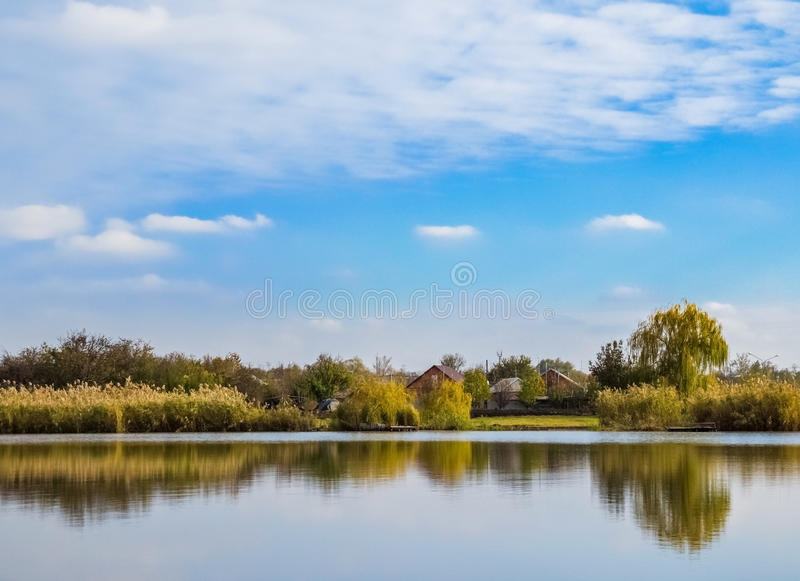 与房子的Lanscape临近湖在蓝天下 免版税库存照片