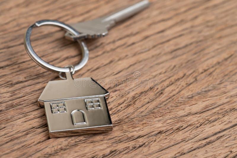 与房子钥匙圈的在木桌上的回归键或keychain使用作为房主,抵押或买卖物产和不动产 免版税图库摄影