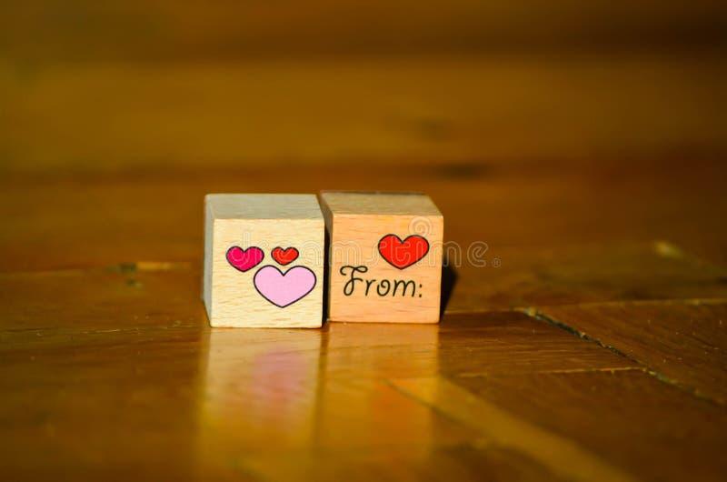 与手书面题字的木立方体从与红色和桃红色心脏的心脏 免版税库存图片